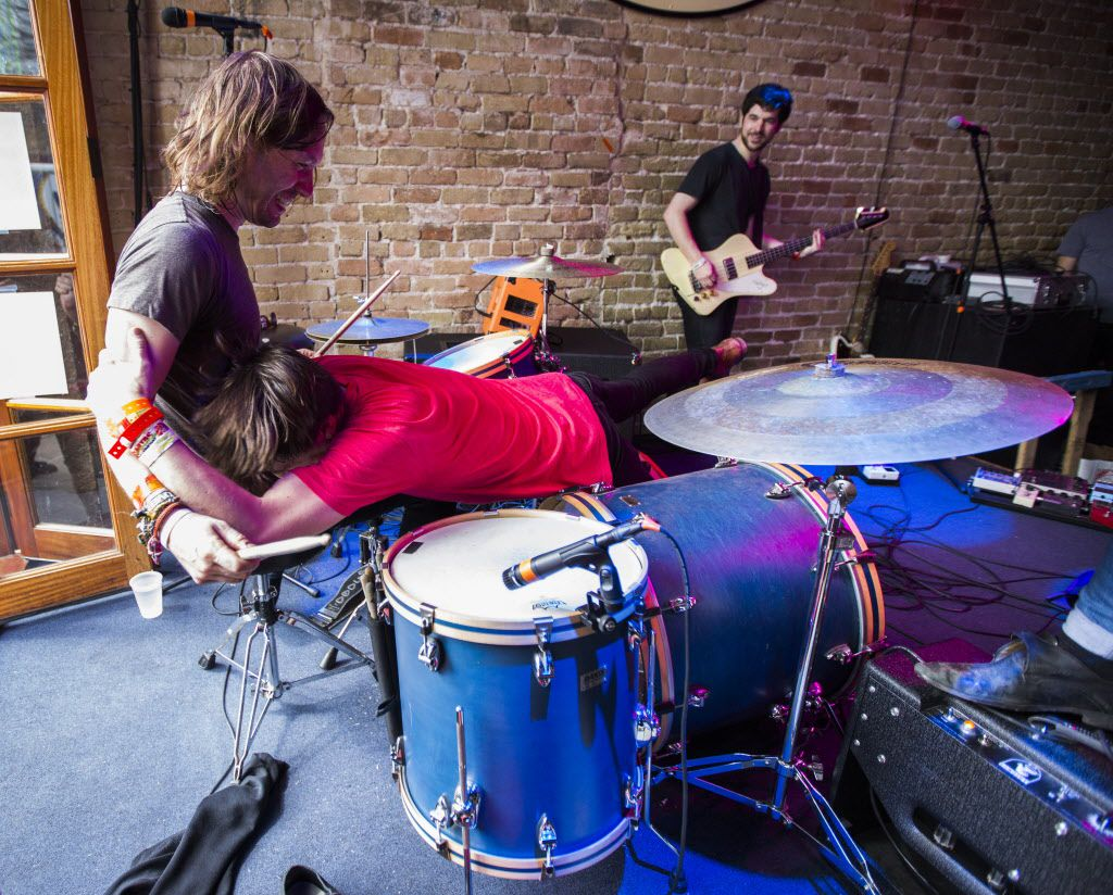 Guitar player and vocalist Billy Yost, dives on to his drummer, Ryan Farnham, during a performance by their band, The Kickback, at Bat Bar on Thursday.