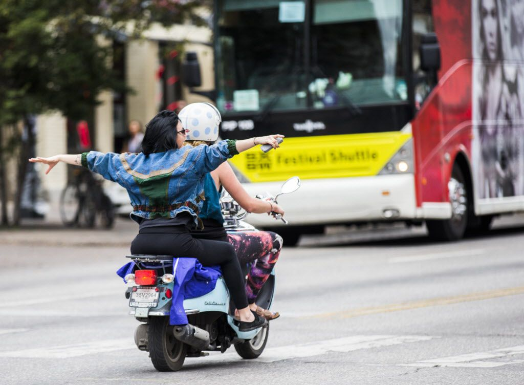 Two women ride a scooter down Congress Avenue during the 2015 SXSW interactive and film festival.