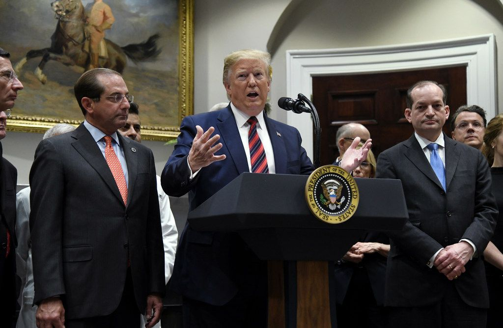 President Donald Trump, flanked by Health and Human Services Secretary Alex Azar (left) and Labor Secretary Alexander Acosta , delivers remarks on ending surprise medical billing in the Roosevelt Room of the White House.