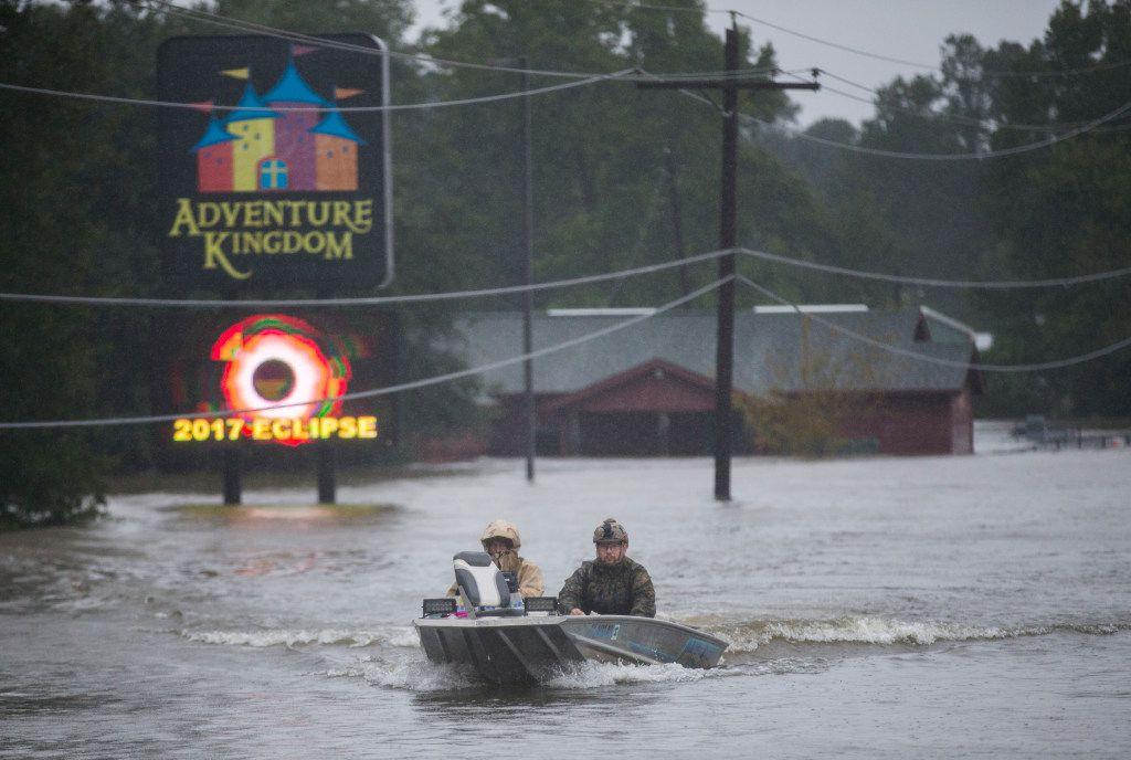Emergency responders drive a boat across Highway 96 in floodwaters in Lumberton.