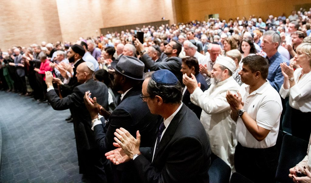 Attendees give a standing ovation as Bradley Laye, president and CEO at the Jewish Federation of Greater Dallas, gives remarks during a community service of hope and healing at Congregation Shearith Israel in Dallas on Oct. 28, 2018.