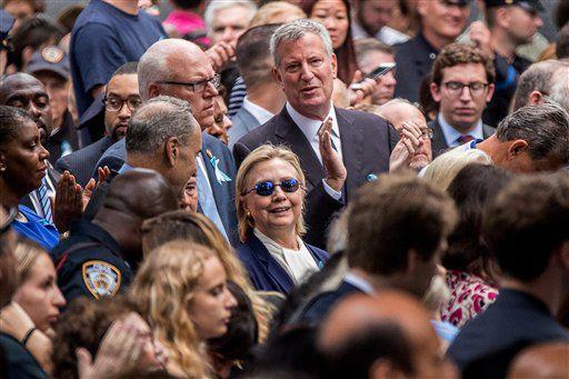 La candidata presidencial demócrata Hillary Clinton, al centro, acompañada por el senador demócrata Chuck Schumer, de Nueva York, al centro a la izquierda, el representante demócrata Joseph Crowley, también de Nueva York, segundo de izquierda a derecha, y el alcalde neoyorquino Bill de Blasio, al centro arriba, participa en una ceremonia en el monumento conmemorativo por los atentados del 11 de septiembre de 2001, en Nueva York, el domingo 11 de septiembre de 2016./AP