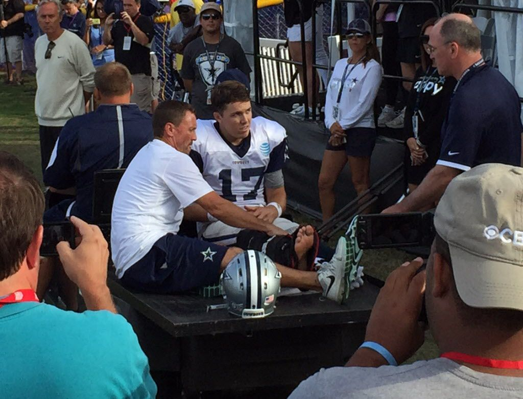 Dallas Cowboys quarterback Kellen Moore (17) listens to the doctor before being carted off the field with a boot on his foot during afternoon practice at training camp in Oxnard, California, Tuesday, August 2, 2016. (Jon Machota/The Dallas Morning News)