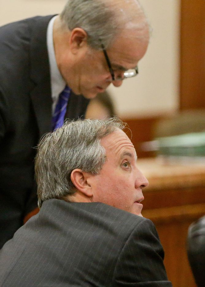 Republican Texas Attorney General Ken Paxton, front, is shown with attorney Phil Hilder during a hearing in the Harris County Criminal District Court, Thursday, July 27, 2017, in Houston. A new trial date of Dec. 11 is set for Paxton to face felony securities fraud charges. The Houston Chronicle reports that jury selection is now expected to start Dec. 1.  (Melissa Phillip/Houston Chronicle via AP)
