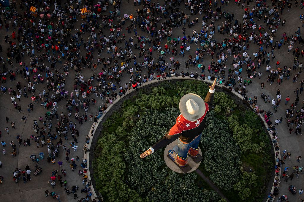 The last rays of sunlight fall over Big Tex as crowds fill the State Fair of Texas in Fair Park on Saturday, Oct. 20, 2018, in Dallas.