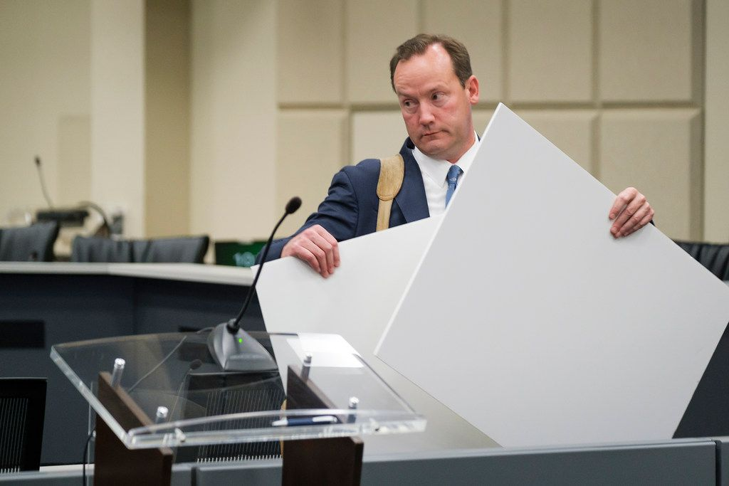 Dallas City Council member Philip Kingston carries exhibits as he departs a briefing room after being cleared by the Ethics Advisory Commission during a hearing at Dallas City Hall.