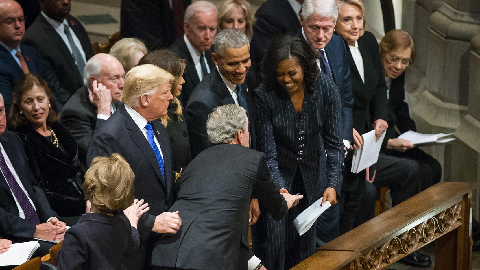 Former President George W. Bush, hands something to a laughing Michelle Obama as (from left) President Donald Trump, first lady Melania Trump, former President Barack Obama, former President Bill Clinton and former Secretary of State Hillary Clinton, look on before Bush took his seat for the State Funeral for George H.W. Bush, the 41st President of the United States, at the Washington National Cathedral on Wednesday, Dec. 5, 2018, in Washington. (Smiley N. Pool/The Dallas Morning News)
