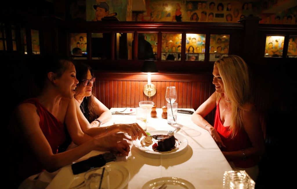 From left: Diana Line, Carol Bernstein and Kamala Bernstein share a dessert at the end of their meal on the last day of business at the Palm Restaurant in Dallas.