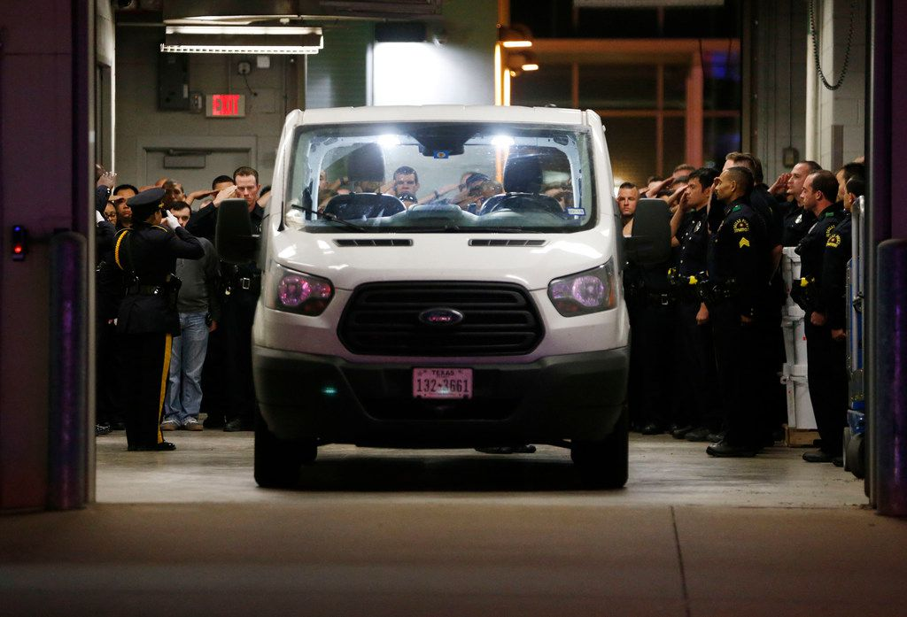 Dallas police officers salute as they move the body of slain Dallas Police Officer Rogelio Santander Jr., at the Dallas County Medical Examiner's office Friday.