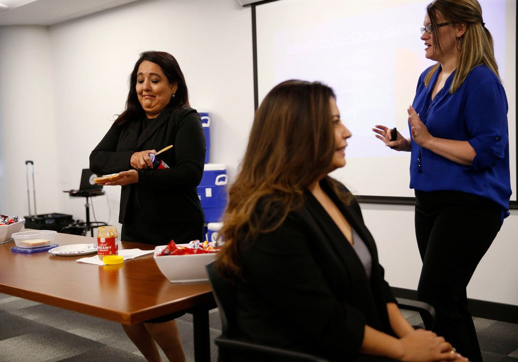 Julissa Faz (left) works on making a peanut butter and jelly sandwich under the direction of Celest Acosta, who has to tell her how to do it without looking in a communication exercise as corporate trainer Holly Van Der Jagt (right) looks on.