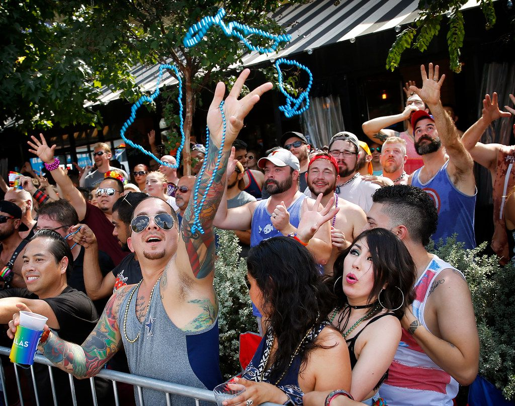 People reach for beads thrown from passing floats during the Texas Freedom Parade, Sunday, September 17, 2017. \