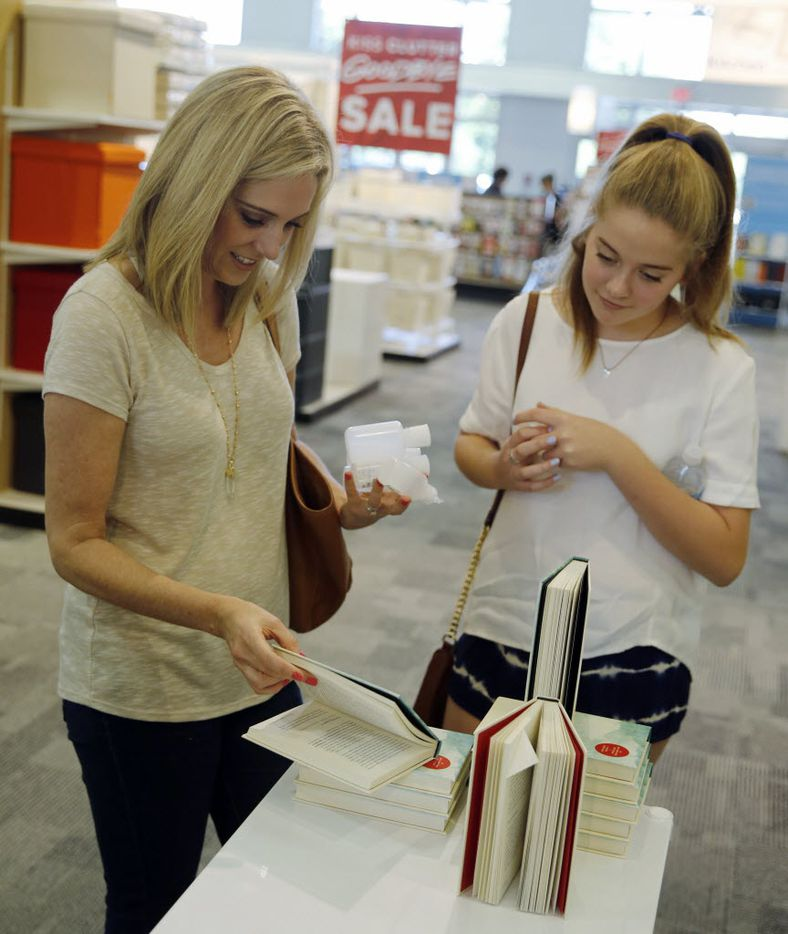 Carey Gidden and her daughter Ellie McClain Gidden take a look at one of the books from Marie Kondo at The Container Store in Dallas on Saturday, April 23, 2016.  (Vernon Bryant/The Dallas Morning News)