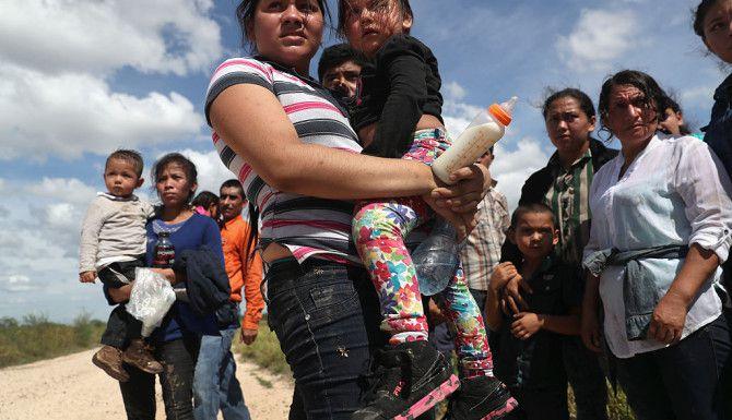 """ROMA, TEXAS. Inmigrantes de América Central esperan a la Patrulla Fronteriza el 17 de agosto de 2016. Miles de familias centroamericanas continúan cruzando el Río Bravo para pedir asilo en Texas. """"Tradicionalmente la gente quiere escapar de la patrulla fronteriza pero cuando están buscando asilo no quieren correr. Quieren encontrar un oficial tan rápido como sea posible porque hace calor y tienen niños, a veces niños enfermos. Cuando me acerqué, los agentes les estaban dando agua y los iban a meter a la patrulla. Es difícil fotografiar la gente cuando está cruzando el río porque los coyotes o contrabandistas no quieren ser identificados por los agentes en el futuro"""". Foto: John Moore / Getty Images."""