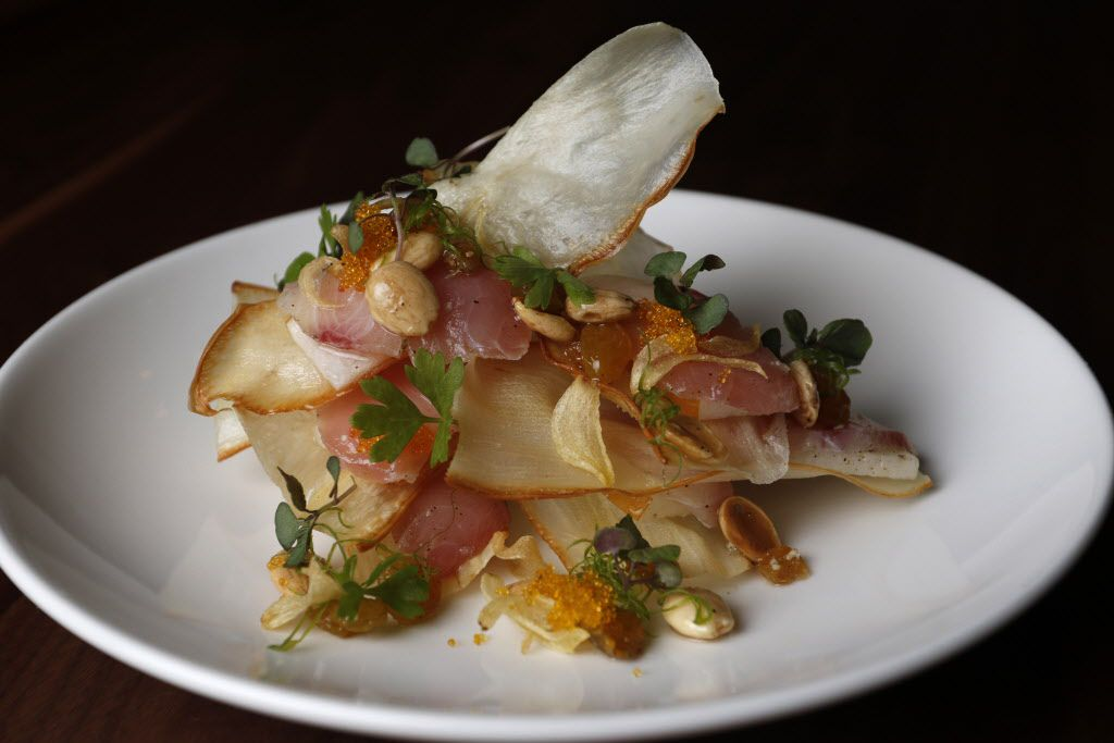 """Machi cure, a signature dish from the original Uchi, is an elegant spin on nachos. It layers yuca crisps, lightly smoked yellowtail (""""machi"""" is short for """"hamachi""""), thin slices of Asian pear, slivered negi (spring onion), Marcona almonds and tobiko (flying fish roe)."""