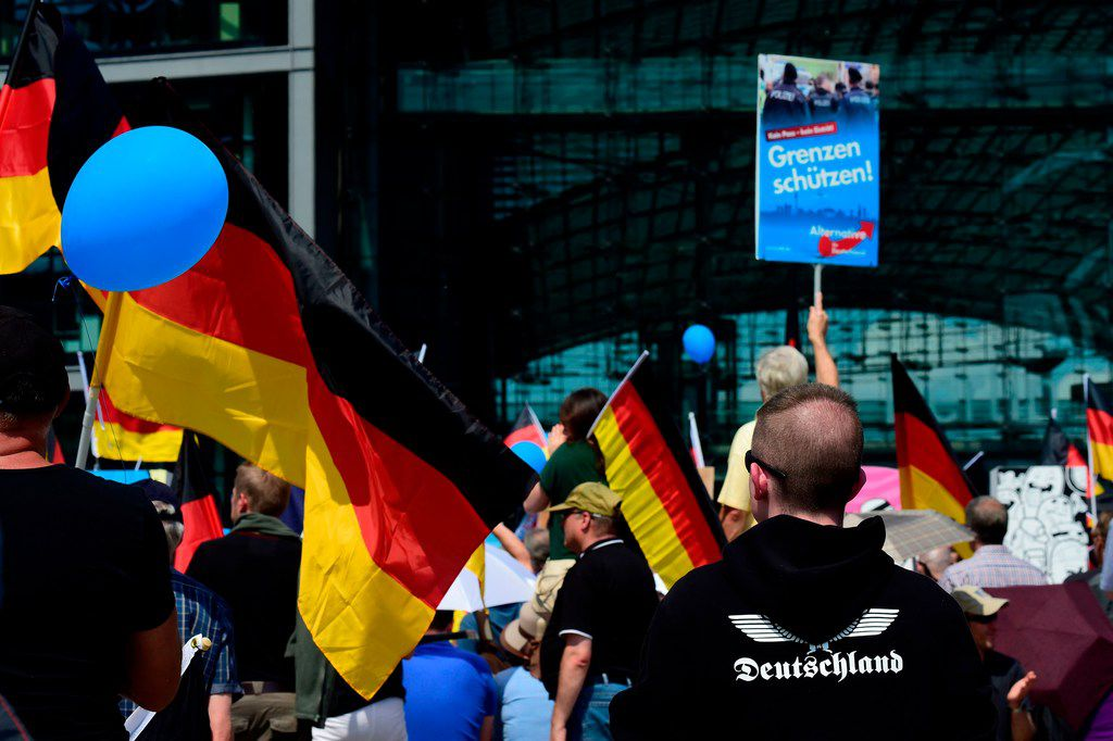 "Alternative for Germany (AfD)'s demonstrators holding AfD and German flags gather at the main station in Berlin to attend the ""demonstration for the future of Germany"" called by the far-right AfD in Berlin on May 27, 2018."