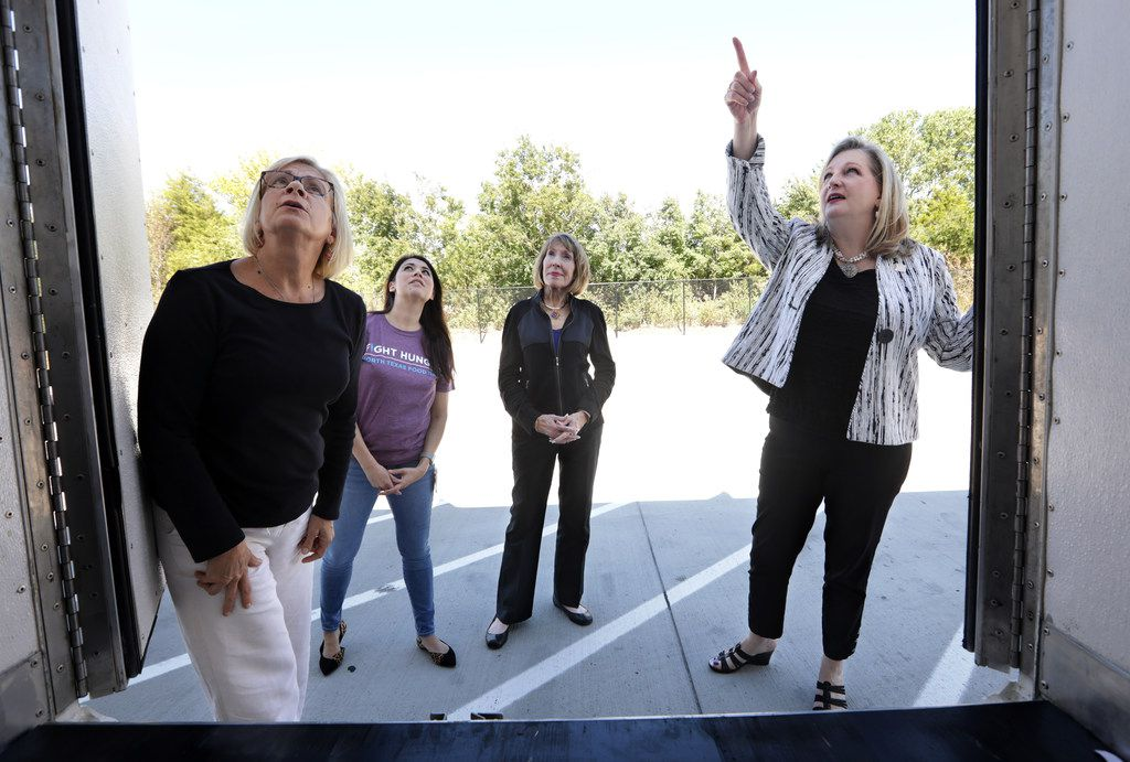 North Texas Food Bank's Dixie Hays, left, and Sara Gorath; Catholic Charities Dallas', Kathy O'Neal; and NTFB's CEO and president Trisha Cunningham examine one of the new deliver trucks at the North Texas Food Bank headquarters in Plano on Monday.