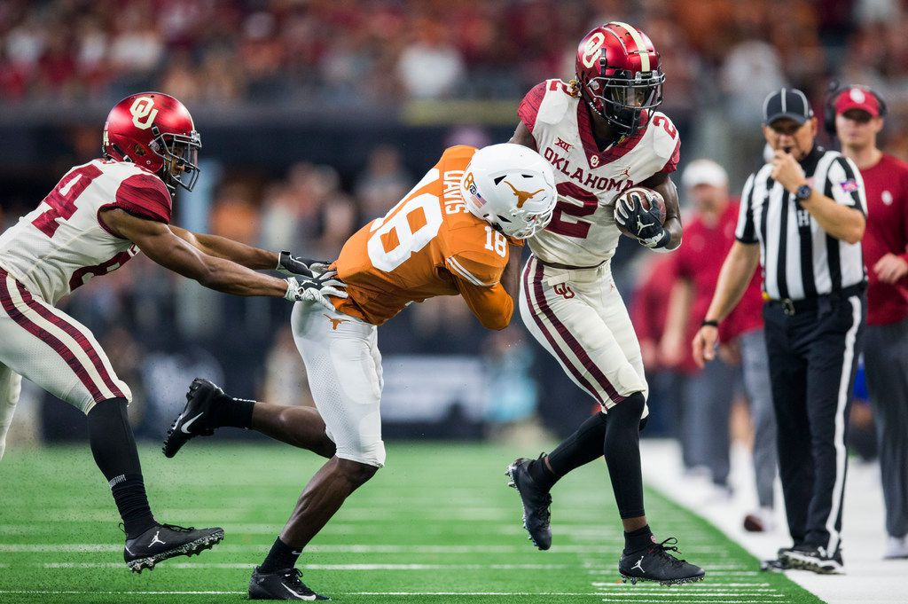 Texas Longhorns defensive back Davante Davis (18) pushes Oklahoma Sooners wide receiver CeeDee Lamb (2) out of bounds during the third quarter of the Big 12 Championship football game between the Texas Longhorns and the Oklahoma Sooners on Saturday, December 1, 2018 at AT&T Stadium in Arlington, Texas. (Ashley Landis/The Dallas Morning News)