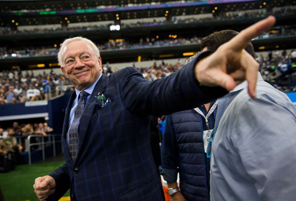 Dallas Cowboys owner Jerry Jones points to a friend on the sideline before an NFL game at AT&T Stadium in Arlington.