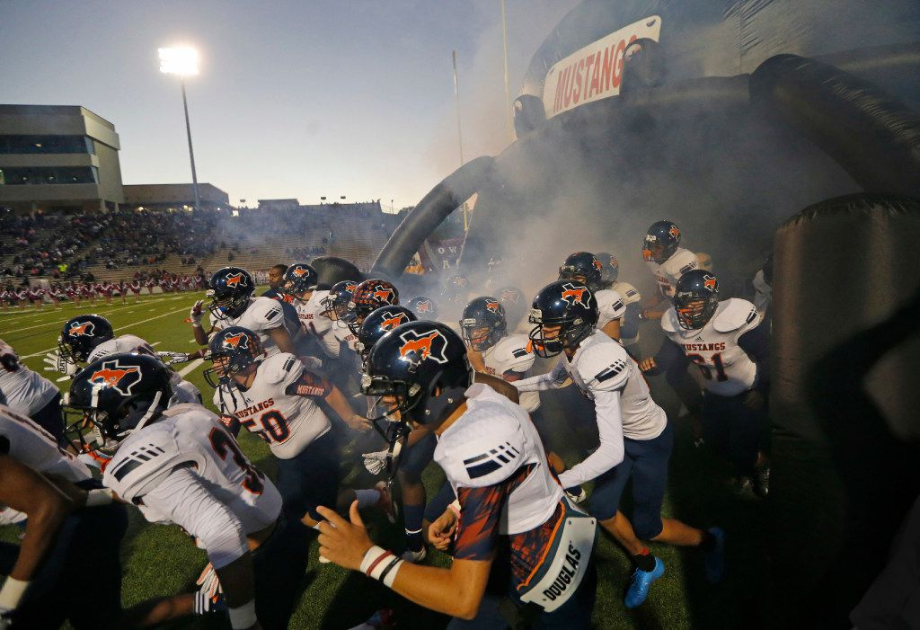 The Sachse Mustangs swarm onto the field before opening kickoff during the Sachse High School Mustangs vs. the Rowlett High School Eagles football game at Homer B. Johnson Stadium in Garland, Texas on Friday, October 21, 2016.