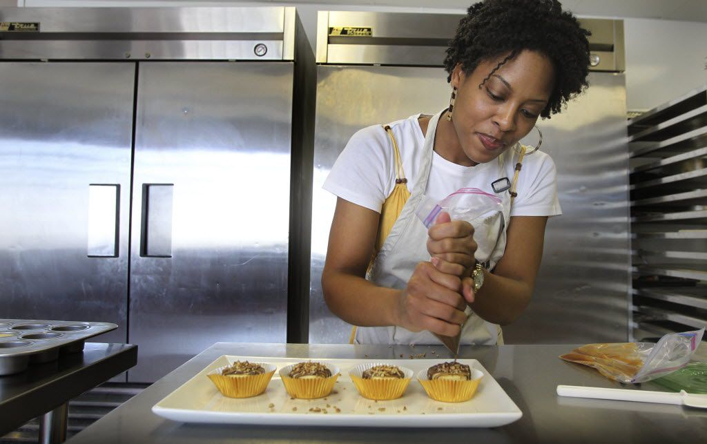 """Juakita Berkley ices the mini-cheesecakes for her small business """"Top That Cheesecake"""" in Garland. (Louis DeLuca/The Dallas Morning News)"""