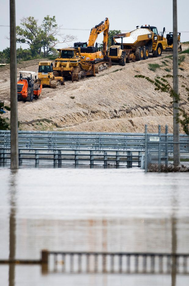 Heavy equipment is staged on an embankment leading up to the levee of the Addicks Reservoir near IH-10 and Eldridge Parkway as flood water from Hurricane Harvey remains next to the roadway on Monday, Sept. 4, 2017, in Houston.