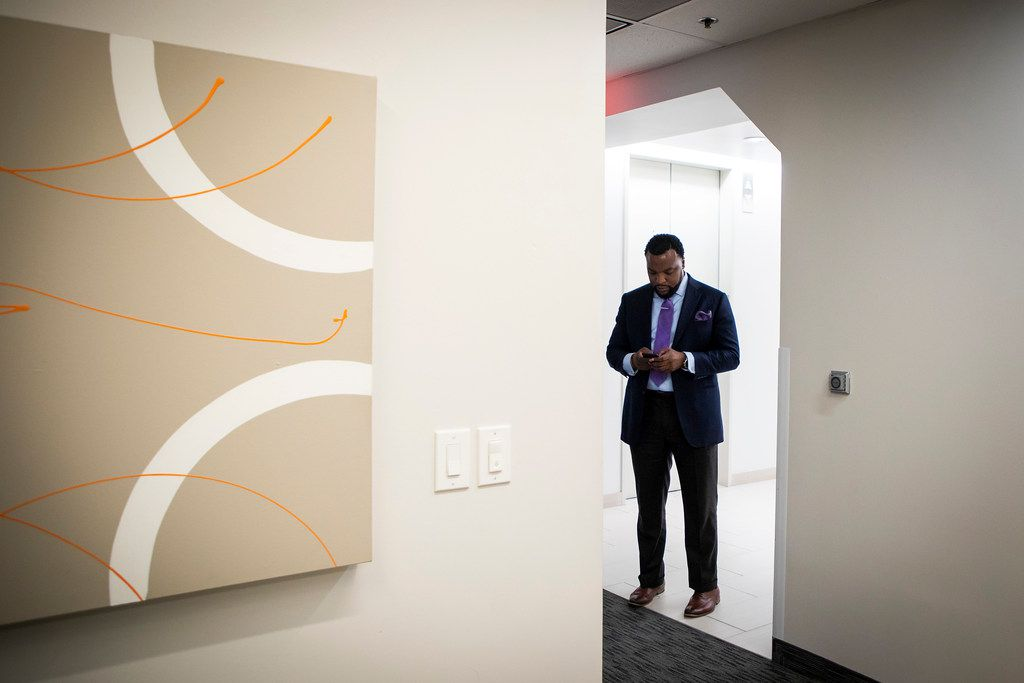 Civil rights attorney Lee Merritt pauses to check a text message on his phone in the hallway of his downtown  Dallas office on June 1.