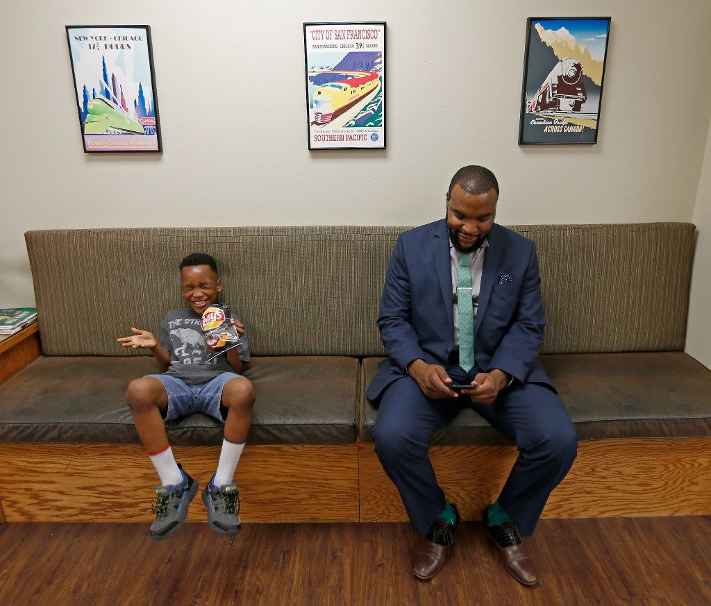 Attorney Lee Merritt shares a laugh with his 7-year-old son, Stacy Merritt Jr., in a waiting room of the North Texas Orthodontic Associates office in Allen.
