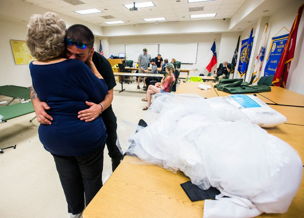 Joyce Brown, office manager of the Lumberton Central Fire Station, hugs firefighter Kyle Parry, who retrieved the wedding dress of his fiancee, Stephanie Hoekstra, from his flooded house.