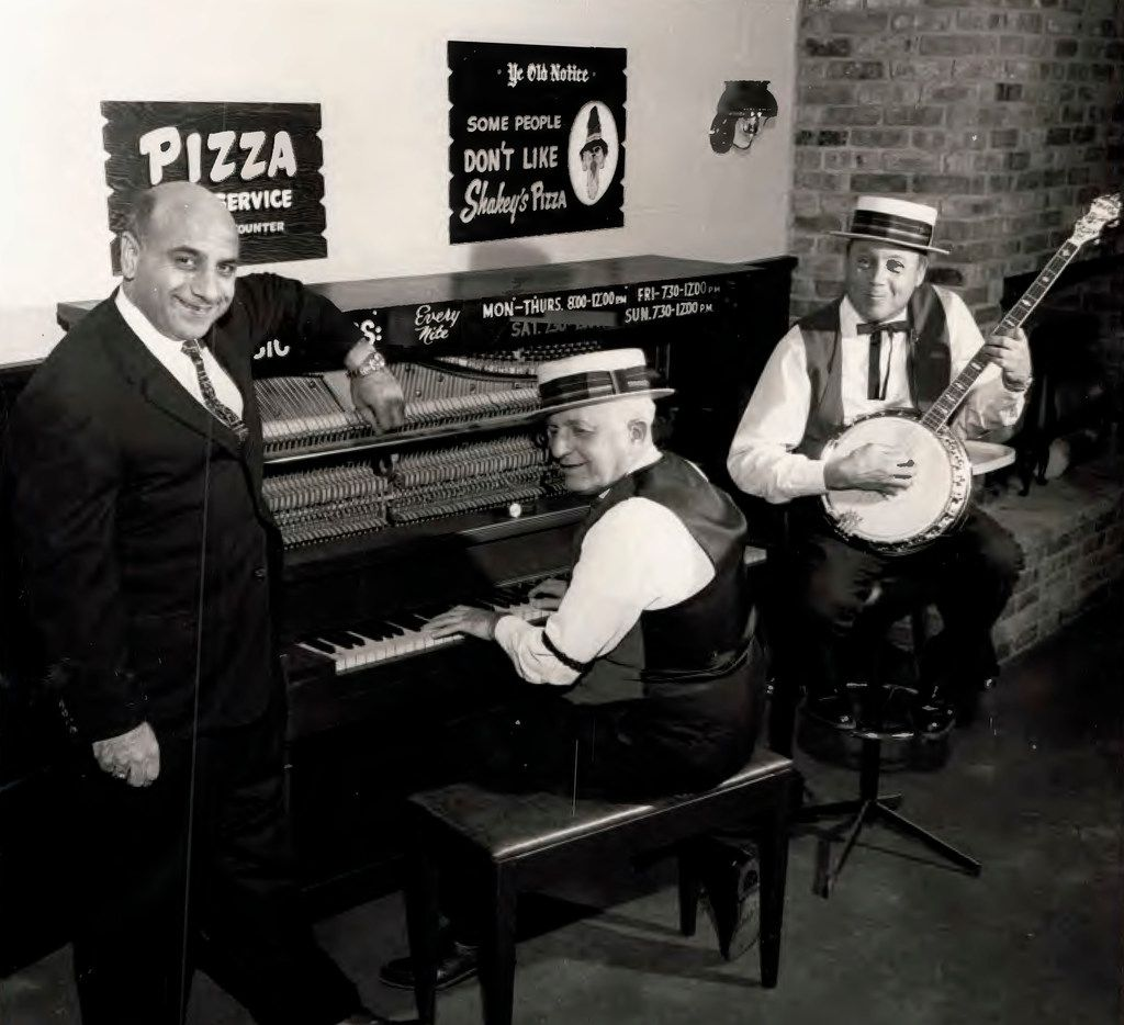 Andy Stasio (left), who opened the first Shakey's Pizza Parlor in DFW on Northwest Highway in the 1960s, poses at that location with banjo and piano players on the set. This photo was taken around 1965-66 and was provided by his son.