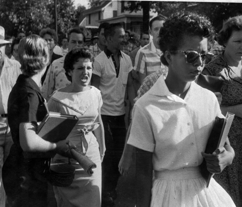 In this Sept. 4, 1957 file photo, students of Central High School in Little Rock, including Hazel Bryan, shout insults at Elizabeth Eckford as she calmly marches down to a line of National Guardsmen, who blocked the main entrance and would not let her enter. (AP Photo/Arkansas Democrat Gazette/Will Counts, File)