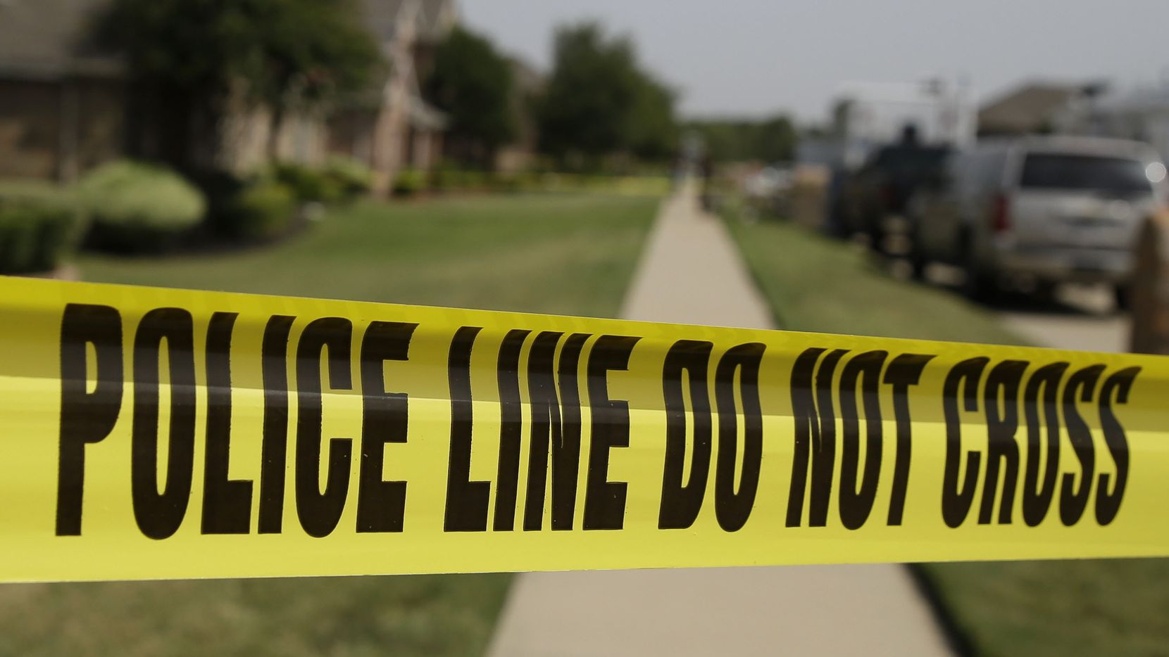 Crime scene tape marks off an area law enforcement investigators were working outside the house of a fatal shooting Aug. 8, 2013, in DeSoto, Texas.