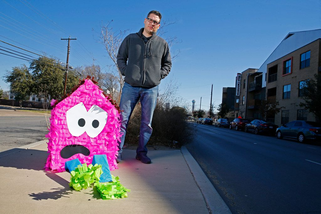 Dallas artist Giovanni Valderas stands next to one of the pieces of his project called Casitas Tristas on Fort Worth Drive in Dallas on Jan. 14.  He creates small houses to call attention to the lack of affordable housing in Oak Cliff, the neighborhood he grew up in.