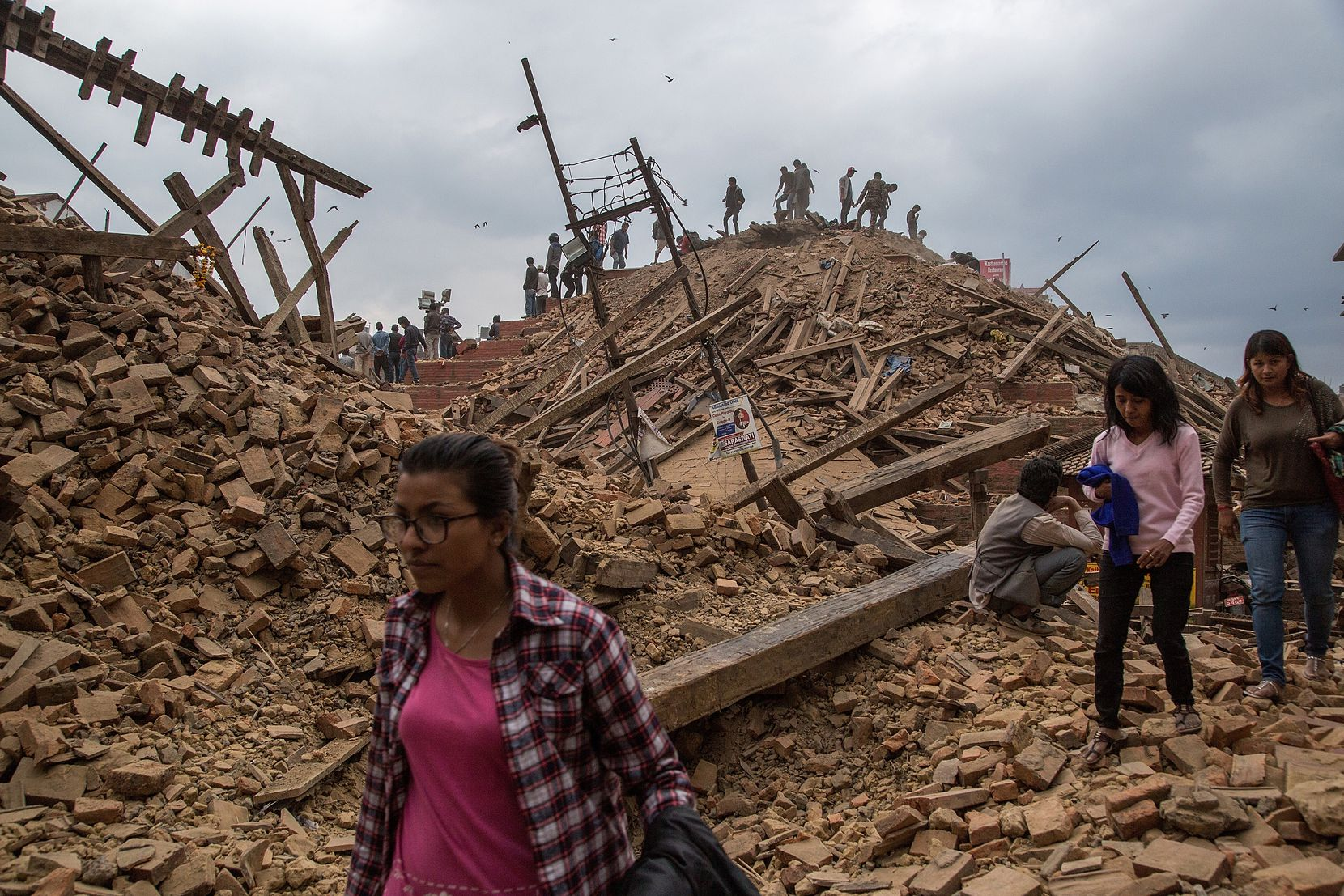 KATHMANDU, NEPAL - APRIL 25: People stand on top of debris from a collapsed building at Basantapur Durbar Square watching the destruction following an earthquake on April 25, 2015 in Kathmandu, Nepal. A major 7.8 earthquake hit Kathmandu mid-day on Saturday, and was followed by multiple aftershocks that triggered avalanches on Mt. Everest that buried mountain climbers in their base camps. Many houses, buildings and temples in the capital were destroyed during the earthquake, leaving hundreds dead or trapped under the debris as emergency rescue workers attempt to clear debris and find survivors.  (Photo by Omar Havana/Getty Images) *** BESTPIX ***