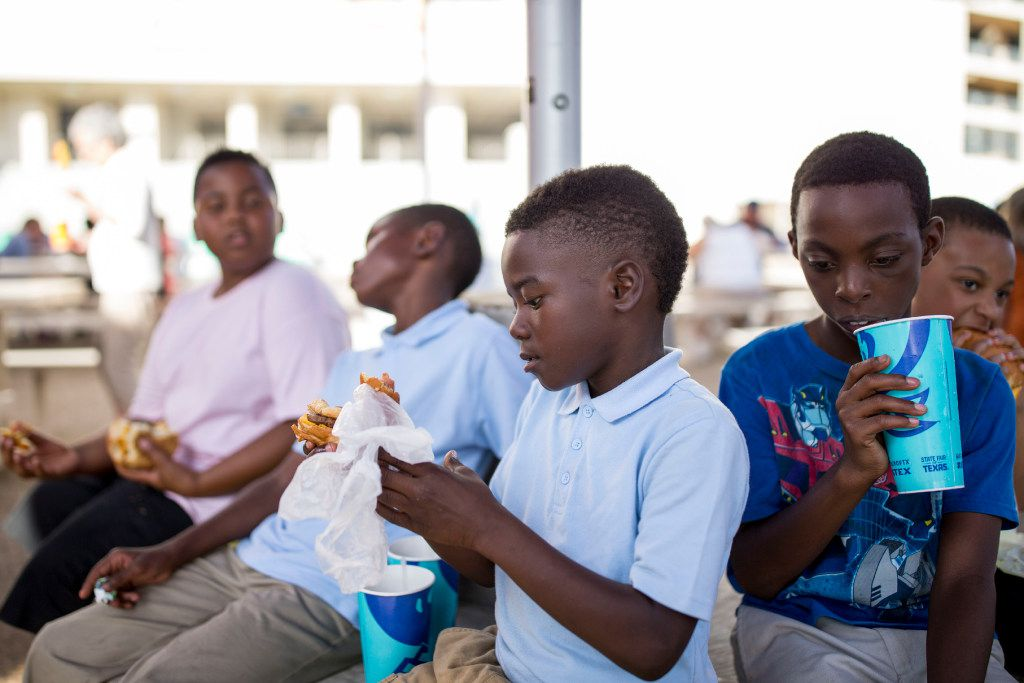 Eric Belin (center), 9, eats hamburger as Jakoree Smith (right), 10, sips on a beverage as several students from Paul L Dunbar Elementary School was taken on a visit to the State Fair of Texas at Fair Park on Oct. 19, 2016 in Dallas.
