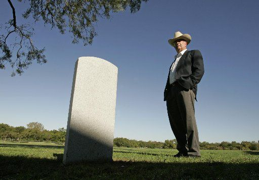 In this 2006 file photo, John Neely Bryan, great-great-grandson of the Dallas founder, stands by the headstone that will be dedicated Saturday at the Austin State Hospital Cemetery in Austin.