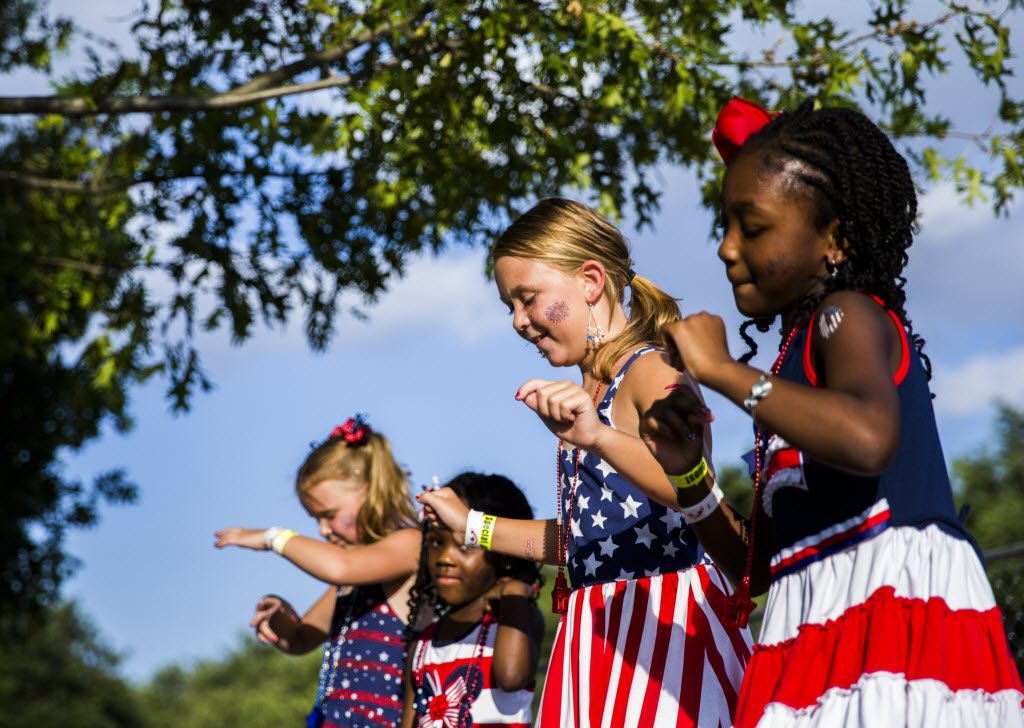 From left: Kate Gust, 6, Emme Mathews, 4, Lauren Gust, 9, and Olivia Mathews, 7, dance together during the Addison Kaboom Town! festival and fireworks show on Sunday, July 3, 2016 at Addison Circle Park in Addison, Texas.  (Ashley Landis/The Dallas Morning News)