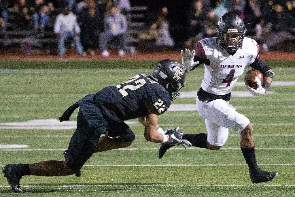 Wolves' running Montaye Dawson (4) attempts to stiffarm Cougars' cornerback Christian Gonzalez (22) while playing in a high school football game at Tommy Briggs Cougar Stadium at The Colony, Texas on Friday, November, 16, 2018. Mansfield Timberview was beating the The Colony Cougars 21-17 at the end of the first half. (Daniel Carde/The Dallas Morning News)
