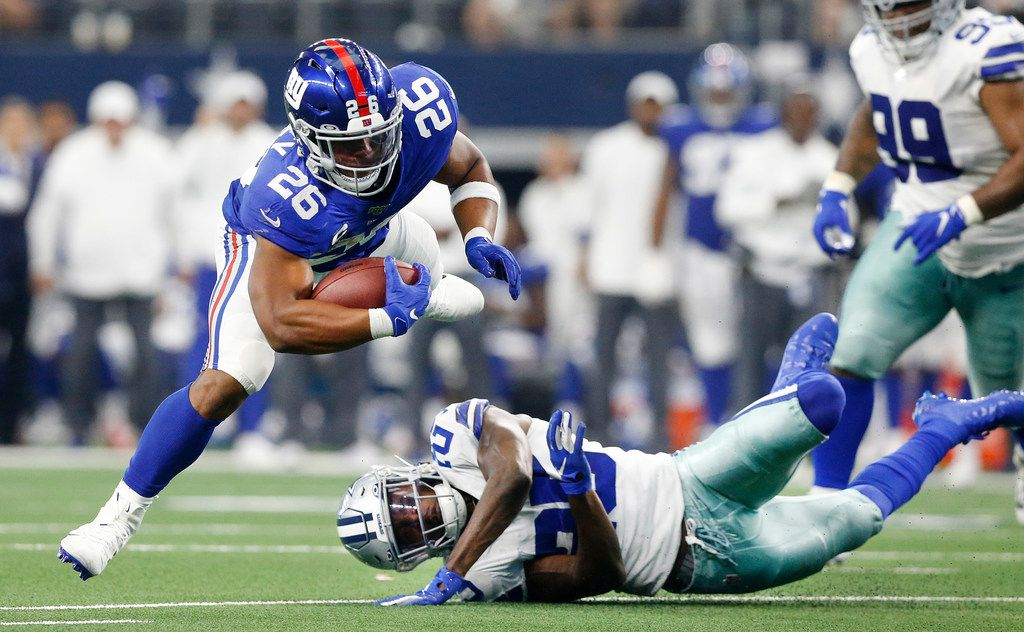 Dallas Cowboys free safety Xavier Woods (25) trips up New York Giants running back Saquon Barkley (26) during the third quarter at AT&T Stadium in Arlington, Texas, Sunday, September 8, 2019.