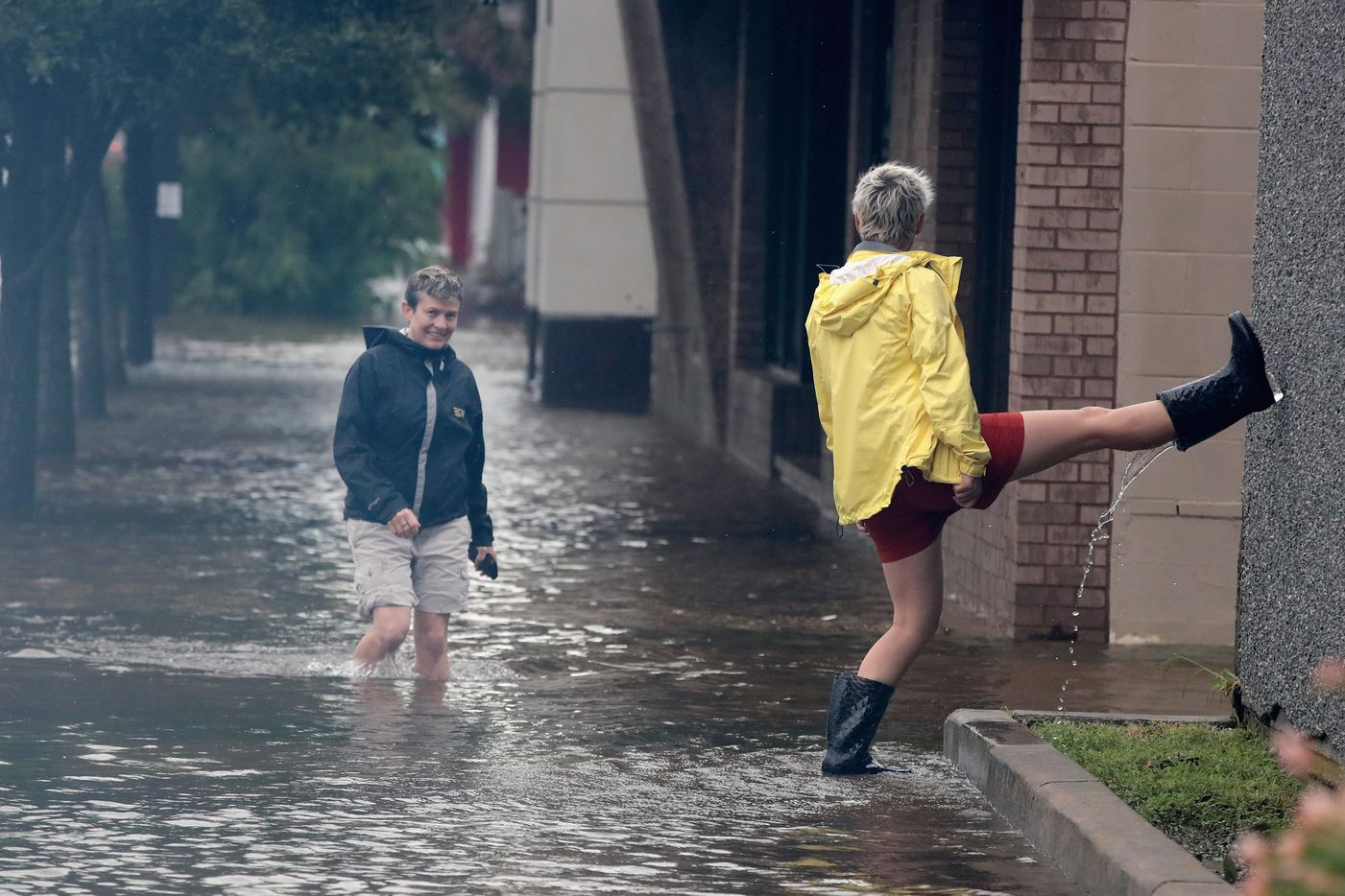 Residents walk along a street flooded by rain from Hurricane Harvey on August 26, 2017 in Galveston, Texas. Harvey, which made landfall north of Corpus Christi late last night, is expected to dump upwards to 40 inches of rain in Texas over the next couple of days.
