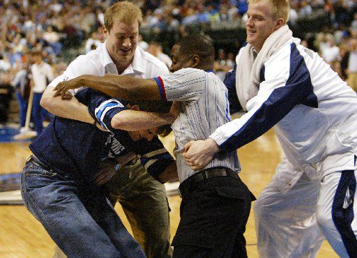 ---   APRIL FOOLS Mavericks  owner Mark Cuban fights with an actor/referee while Mavs' Evan Eschmeyer, right, moves in to restrain the two. The staged melee was Cuban playing  a joke on fans during the New Orleans Hornets game  at the AA Center. photo by MICHAEL MULVEY, DMN