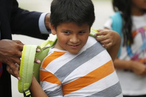 Apolinar López, de 8 años, con su nueva mochila. Adán Gonzáñez, maestro y director de Si Se Puede Network, en Oak Cliff, repartió cientos de mochilas en su barrio. ROSE BACA/DMN