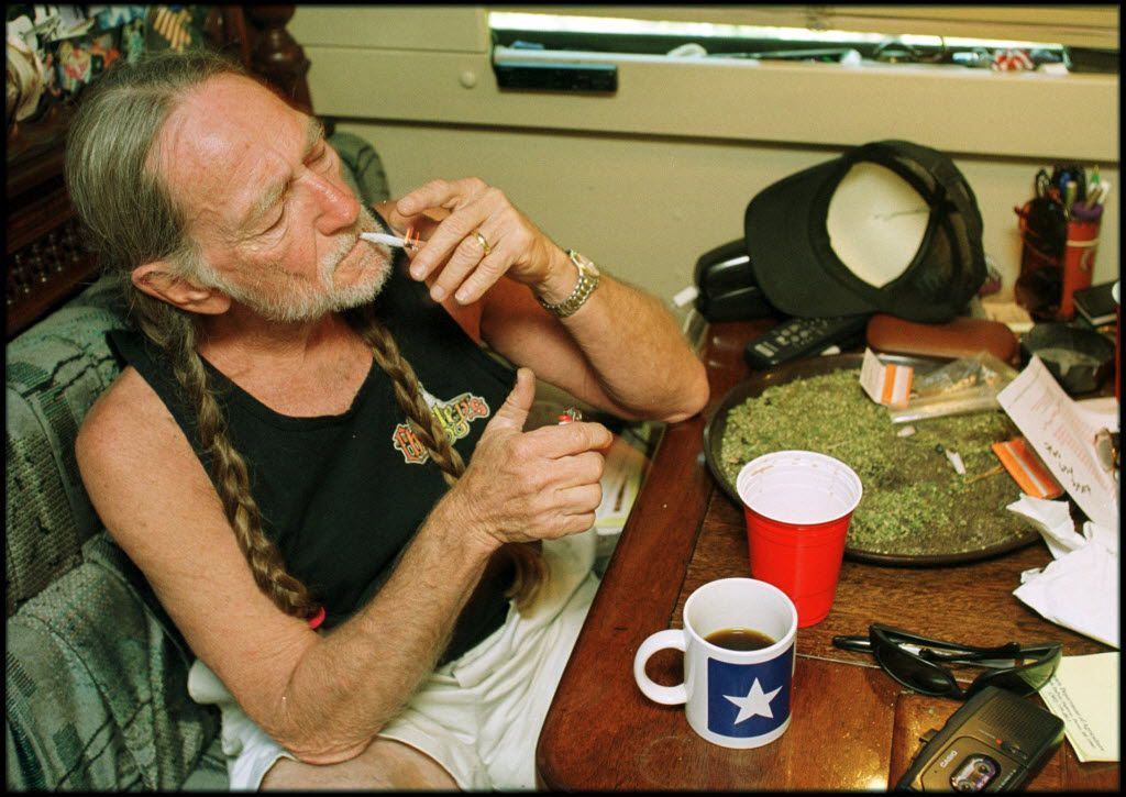 Country singer Willie Nelson takes a drag off a joint while relaxing at his home in Texas. A large amount of marijuana is spread out on the table before him.