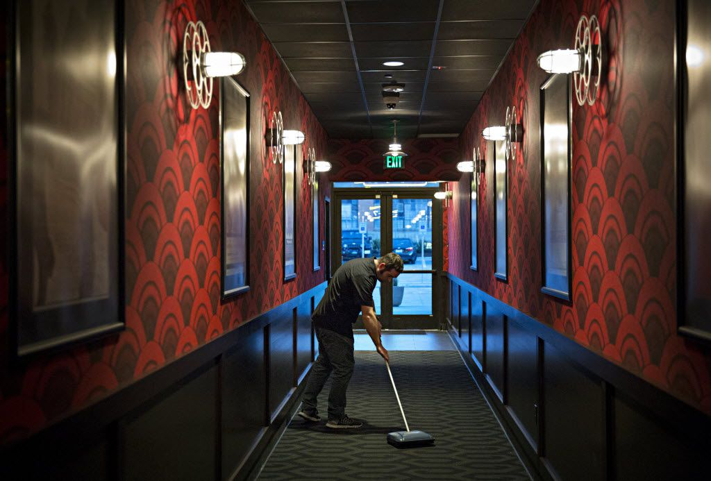 Matt Stubanas, a concierge at Alamo Drafthouse, uses a carpet sweeper as he and other employees prep for a soft opening at the movie chain's new location February 17, 2016 in Dallas. (G.J. McCarthy/The Dallas Morning News)