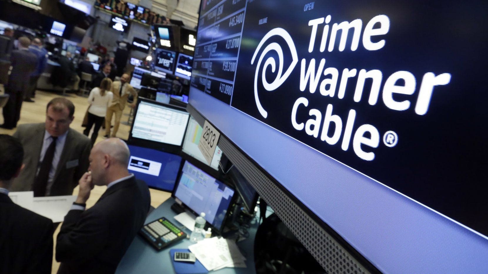 In this Tuesday, May 17, 2016, photo, the Time Warner Cable logo appears above the post where it trades on the floor of the New York Stock Exchange. Charter Communications is closing on its $67 billion acquisition of Time Warner Cable and Bright House Networks. The deals make Charter the second-largest home Internet provider and third-largest video provider in the U.S. Charter says its Spectrum brand will replace the Time Warner Cable and Bright House brands over the next 18 months or so. The name Time Warner will eventually be phased out and the company will be known as Charter Communications. (AP Photo/Richard Drew)