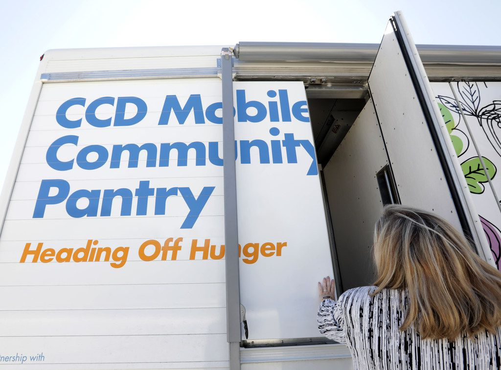 Trisha Cunningham examines one of the new Catholic Charities mobile food pantries at the North Texas Food Bank headquarters in Plano on Monday.