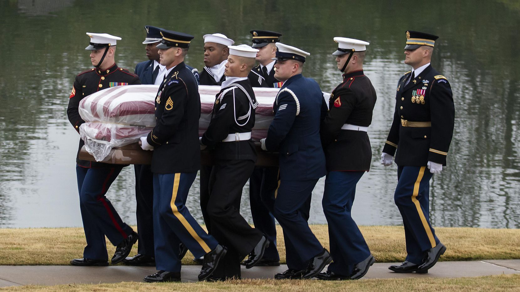 The flag-draped casket of President George H.W. Bush is carried to a burial plot close to his presidential library for internment on Thursday, Dec. 6, 2018, in College Station, Texas.