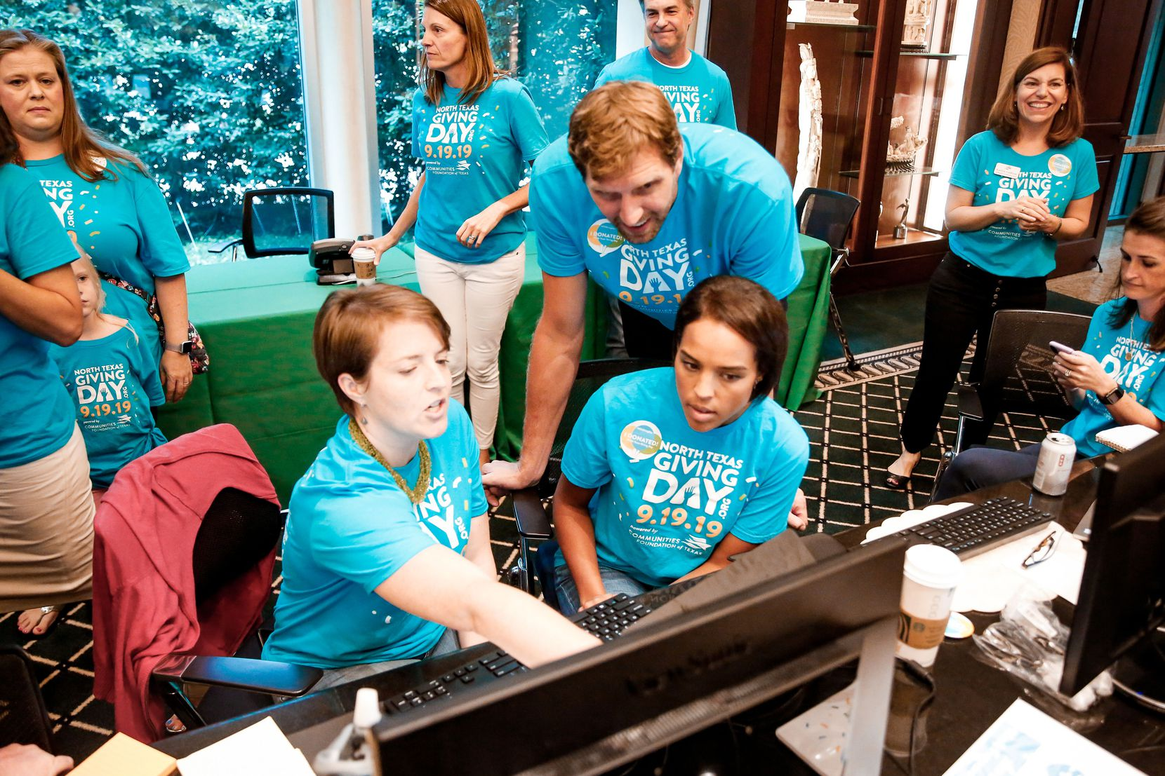 Dallas Mavericks legend Dirk Nowitzki and his wife Jessica (right) monitor totals during North Texas Giving Day.