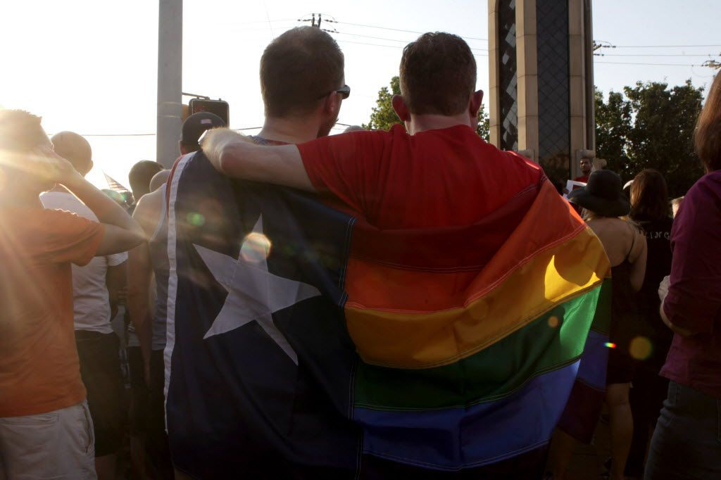 """Jacob Gerber, left and Brandon Kirk wrapped their """"Texas Pride"""" flag around them at the Legacy of Love Monument on June 26, 2013 in Dallas. (File 2013/The Dallas Morning News)"""