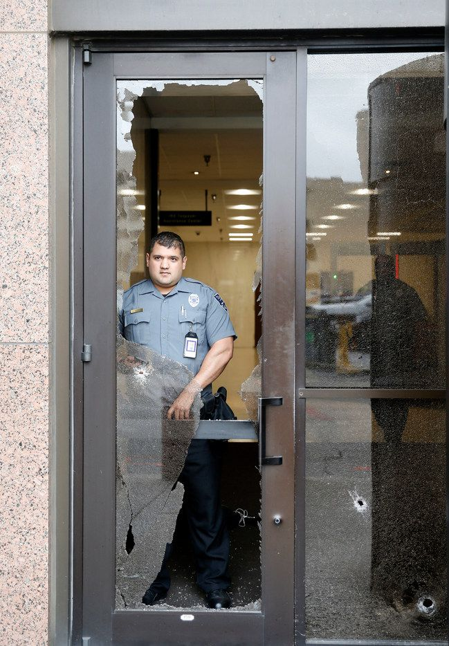A security officer looks out from shattered glass after shots were fired Monday morning, June 17, 2019 at the Earle Cabell federal courthouse in downtown Dallas. Law enforcement returned fire and the shooter was hit by gunfire. No officers or citizens were injured.