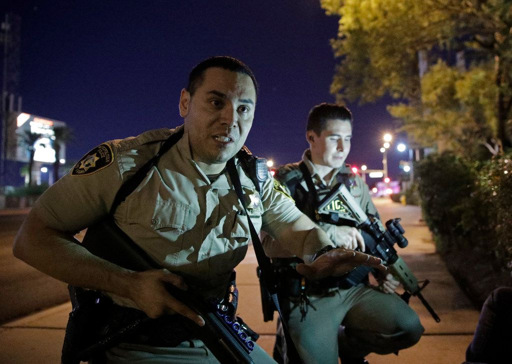 Police advise people to take cover at the scene of a shooting near the Mandalay Bay resort and casino on the Las Vegas Strip.